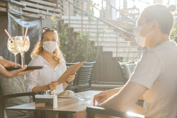 Couple with medical facemask are keeping social distance in restaurant. Aftermath of covid-19...