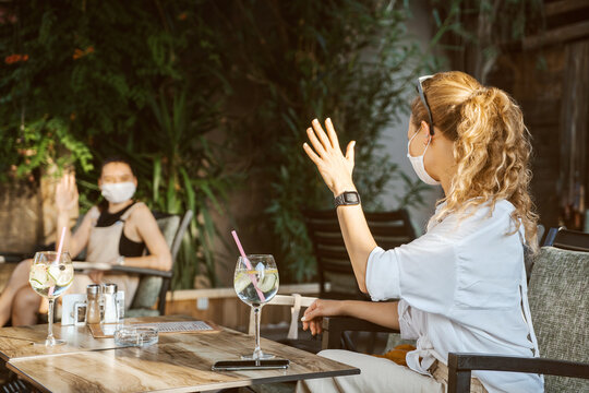 Women with medical facemask are greeting and keeping social distance in restaurant. Aftermath of covid-19 relief of quarantine measures.