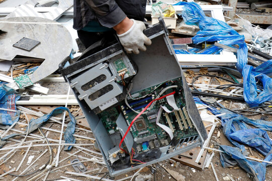 A man carries components of a used computer to obtain recyclable parts at Quan Do village in Bac Ninh province