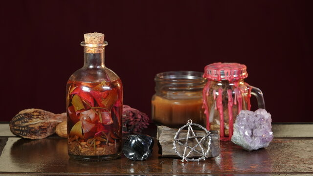Various objects of Wiccan ritual on a stone table - candles, crystals, potion bottle, pentagram