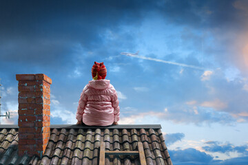 Dreamy little girl sitting alone on the roof