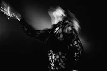 Spiritual dance. Reincarnation freedom. Defocused woman silhouette in transcendent posture on black with blur lights. Fotomurales
