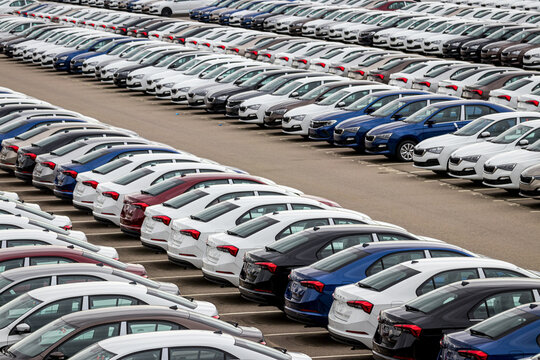 Group Rus, Russia, Kaluga - MAY 24, 2020: Rows of a new cars parked in a distribution center on a cloudy day in the spring, a car factory. Parking in the open air.