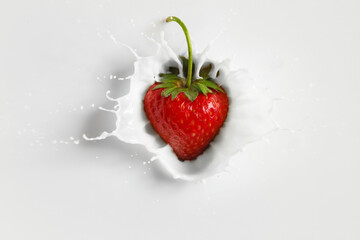 Falling of fresh strawberry into milk