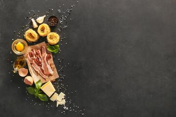 Ingredients for tasty pasta carbonara on dark background