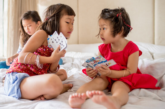 sisters playing cards on a bed