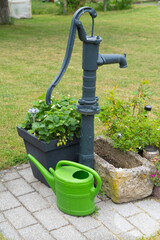 Water pump in the garden with a green watering can