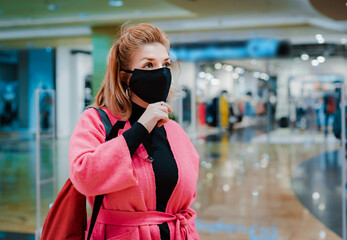 beautiful woman with phone bright pink shopping Mall coat with black protective mask on her face from virus infected air.