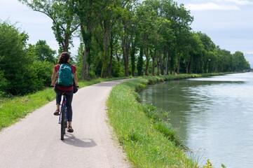 Femme à vélo sur le canal des Deux-Mers