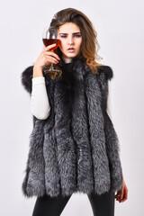 Fashionable lady likes luxury. Fashion model long hair fur coat or vest hold wineglass. Girl enjoy luxury lifestyle attributes. Woman drink wine wear luxury fur clothing. Luxury winery concept
