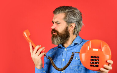 Man with moustache holding vintage phone. vintage communication device. Businessman talking on vintage phone in his office. agile business. vintage stationary telephone. hello 80s