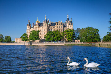 Schwerin Castle looking like a fairy tale castle surrounded by a wonderful landscape composed of lakes and forests