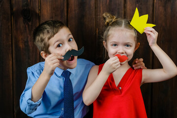 A kid with props for a photo booth. Children with the requisite mustache on wooden background....