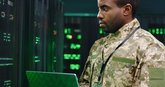 Close up of African American male army technician in camouglage costume and hat typing on keyboard of laptop computer while working with secret data at server room. Government analytic center.