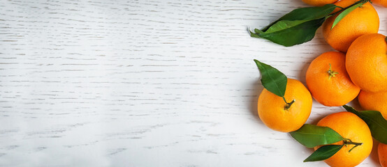 Fototapete - Fresh ripe tangerines with leaves and space for text on white wooden table, top view. Banner design