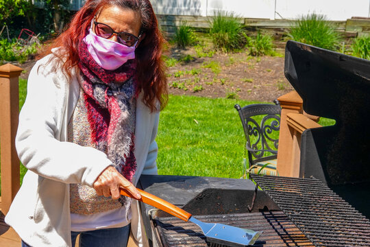 Caucasian woman with long red hair wearing a pink protective face mask cleans a dirty outdoor grill in her backyard