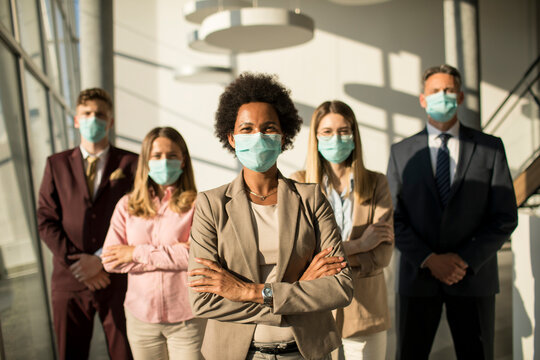 Group of asian business people standing in office and wear mask for protect prevent infection by corona virus