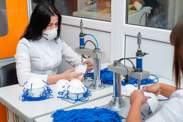 Women work at a machine for the manufacture of medical masks with nanofiber and solder loops to them with ultrasound. Coronovirus and Covid-19 Prevention