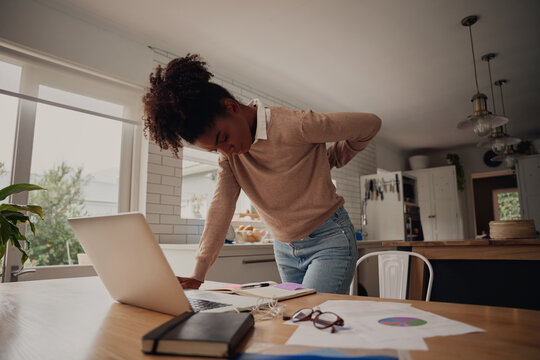 Young afro woman standing suffering from back pain while working on laptop at home