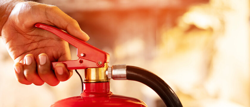 hand presses the trigger fire extinguisher available in fire emergencies conflagration damage background. Safety