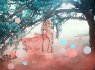 Art princess elf stands swinging on magical forest swing mystical tree. Woman nymph in long pink dress skirt fluttering fly wind. Fantasy nature white blue balls, air balloons. red fog colorful smoke.