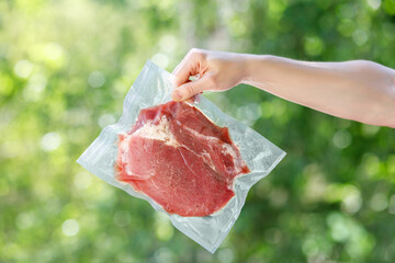 Hand shows packaged meat in a vacuum bag .
