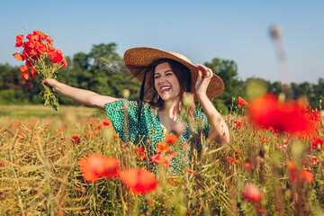 Young laughing woman raised arm holding bouquet of poppies flowers walking in summer field. Happy girl feeling free