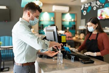 Man Applying Sanitizer On Hand In Cafe