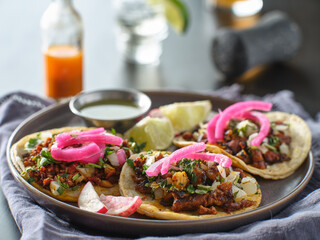 Wall Mural - mexican carne asada tacos with pink pickled onions on plate