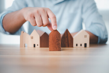 Real estate investment businessman hand choosing mini wood house model from model on wood table, Planning to buy property. concept of Choose the best.