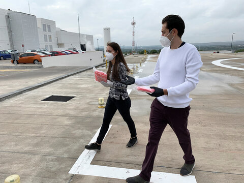 Employees of Sincronia Logistica carry packages of personal protective gear and other essential equipment, before being loaded to a drone for delivery at a public hospital, in Queretaro