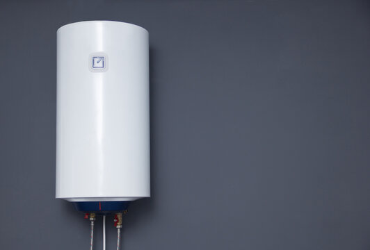 Modern electric boiler on a gray plain wall. White water heater. Space for text