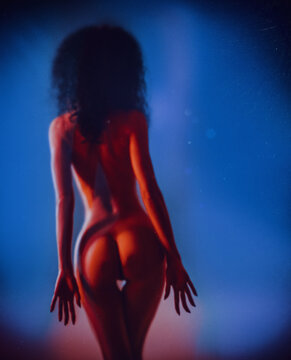 Nude woman at frosted glass