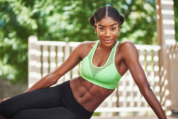 african american woman wearing workout clothes posing on backyard deck