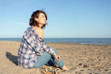 A cheerful dark-haired woman in jeans and a shirt smiles,sitting on the  beach and enjoys the bright sun on a summer day. Concept of summer holidays at sea and live style