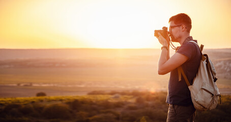 Man photographer with backpack and camera taking photo of sunset mountains