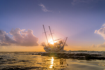 Tuinposter Schipbreuk Sailing boat wreck at sunset