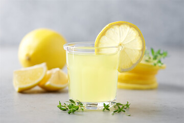 Glass of limoncello traditional Italian alcoholic drink decorated with thyme. Light gray background, close-up view