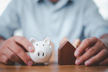 businessman holding a piggy bank and a house model for saving and investment ideas Stock Market Real Estate.