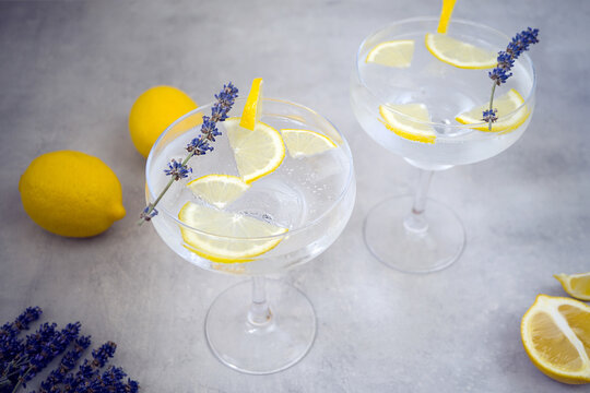 Lemon non-alcoholic cocktails with ice cubes in beautiful glasses for margaret stands on a gray concrete background. Glasses are decorated with lavender and a slice of lemon. Nearby lies two lemons.