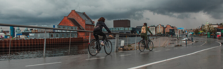 Panoramic crop of people cycling on urban street near canal with cloudy sky at background in Copenhagen, Denmark