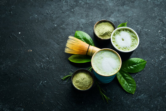 Green tea matcha latte art in a cup on a black stone background. Asian drinks. Top view.
