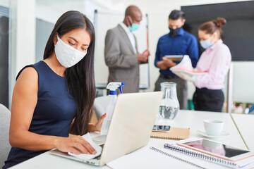 Business Frau mit Mundschutz beim Arbeitsplatz desinfizieren