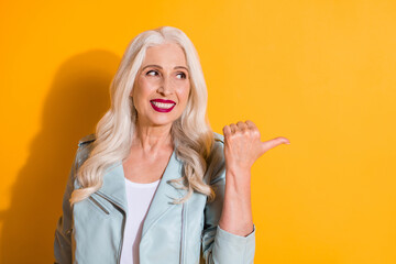 Close up photo portrait of pretty cool stylish grandmother pointing to the side copyspace isolated bright color yellow background