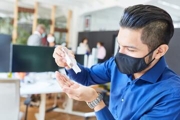 Geschäftsmann mit Mundschutz beim Hände desinfizieren