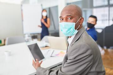 Afrikanischer Geschäftsmann mit Mundschutz und Tablet PC