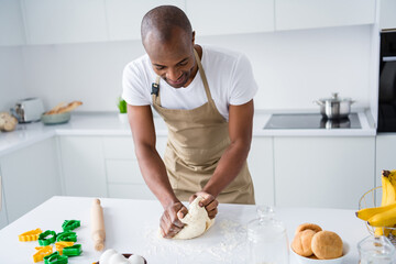 Portrait of nice attractive guy making fresh bread pie pide doughing flour learning practicing courses lesson classes workshop spending free time in modern light white interior house kitchen