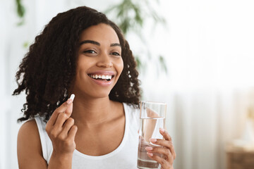 Papiers peints Kiev Healthy Diet Nutrition. Smiling Afro Woman Holding Vitamin Pill And Mineral Water
