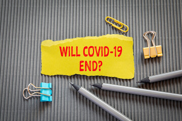 WILL COVID-19 END? Text on torn, yellow paper