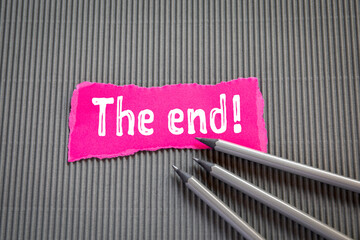THE END! Text on torn, pink paper on corrugated background